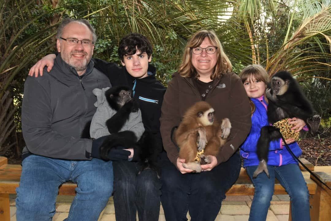 My family of 4 holding 2 black and one brown baby gibbon